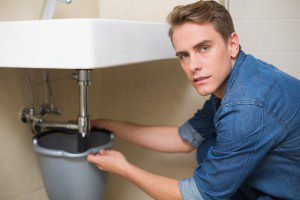 Portrait of handsome plumber repairing the drain of sink in bath